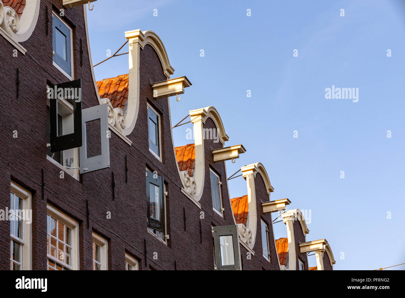 AMSTERDAM, THE NETHERLANDS - AUGUST 6, 2018: A row of Dutch ornate gabled rooftops with moving hooks. - Stock Image
