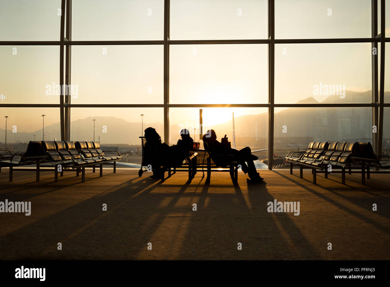 Passenger sitting in a lobby airport waiting for flight - Stock Image