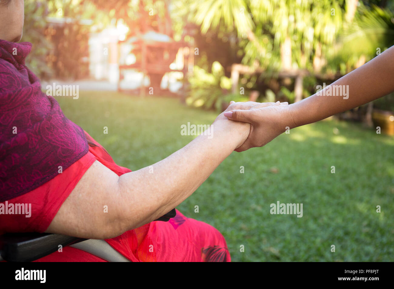 Caretaker pushing senior woman in wheel chair  - Stock Image