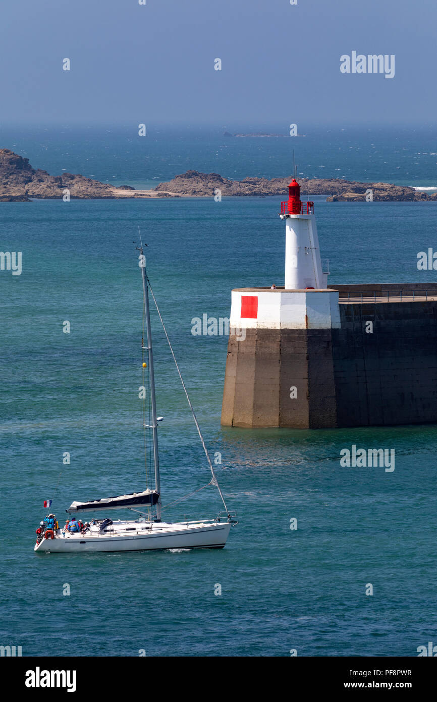 Yacht entering the harbor in the port of Saint Malo on the Brittany coast of northwest France. - Stock Image