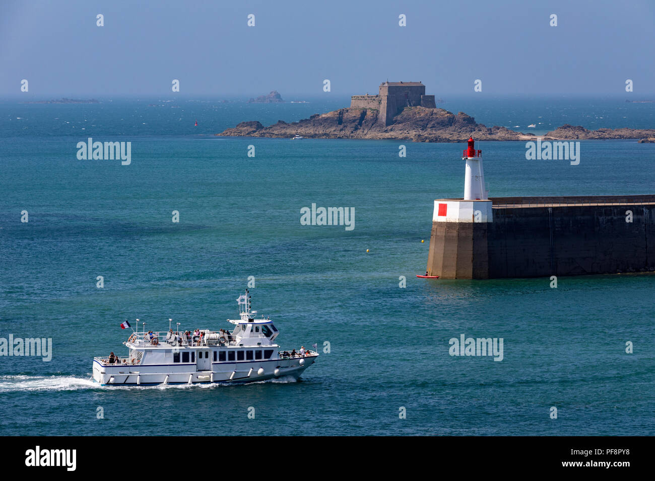 Tour boat entering the harbor in the port of Saint Malo on the Brittany coast of northwest France. The island is Le Petit Be and the fortress dates fr - Stock Image