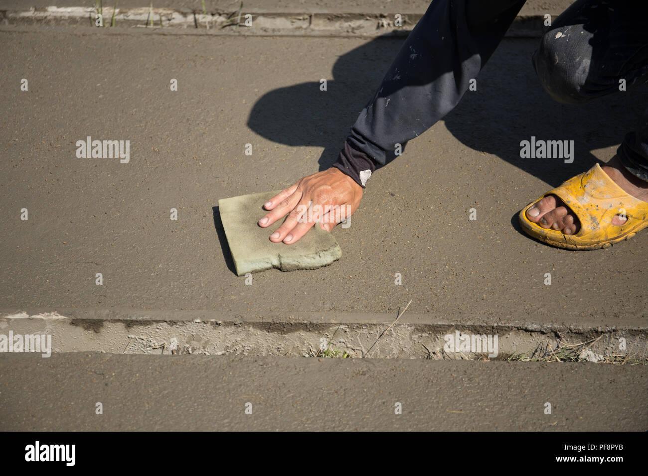 Worker smooth concrete floor with sponge  Stock Photo