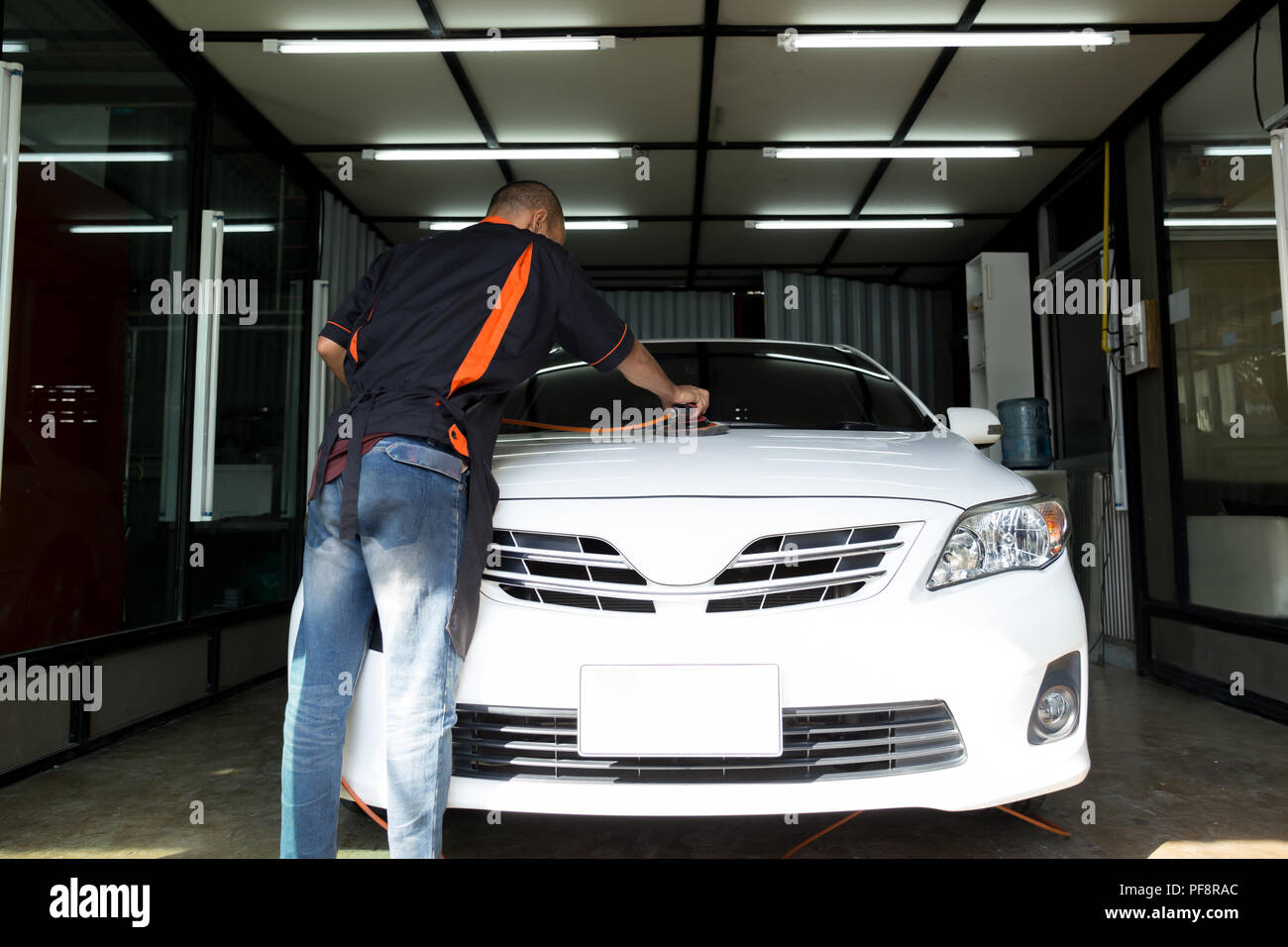 Car care worker polishing the white car  - Stock Image