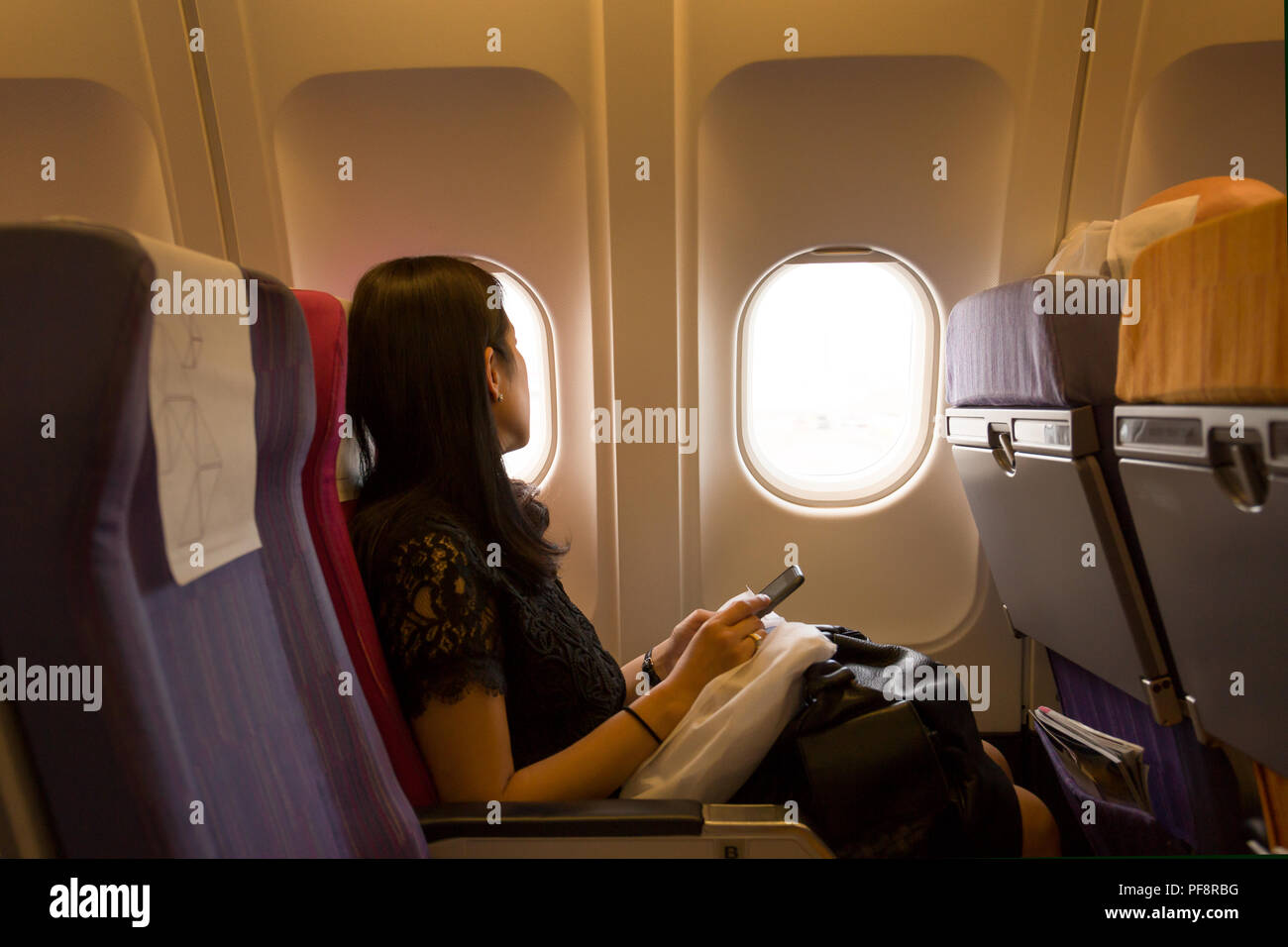 Business woman on plane seat hand holding cell phone - Stock Image