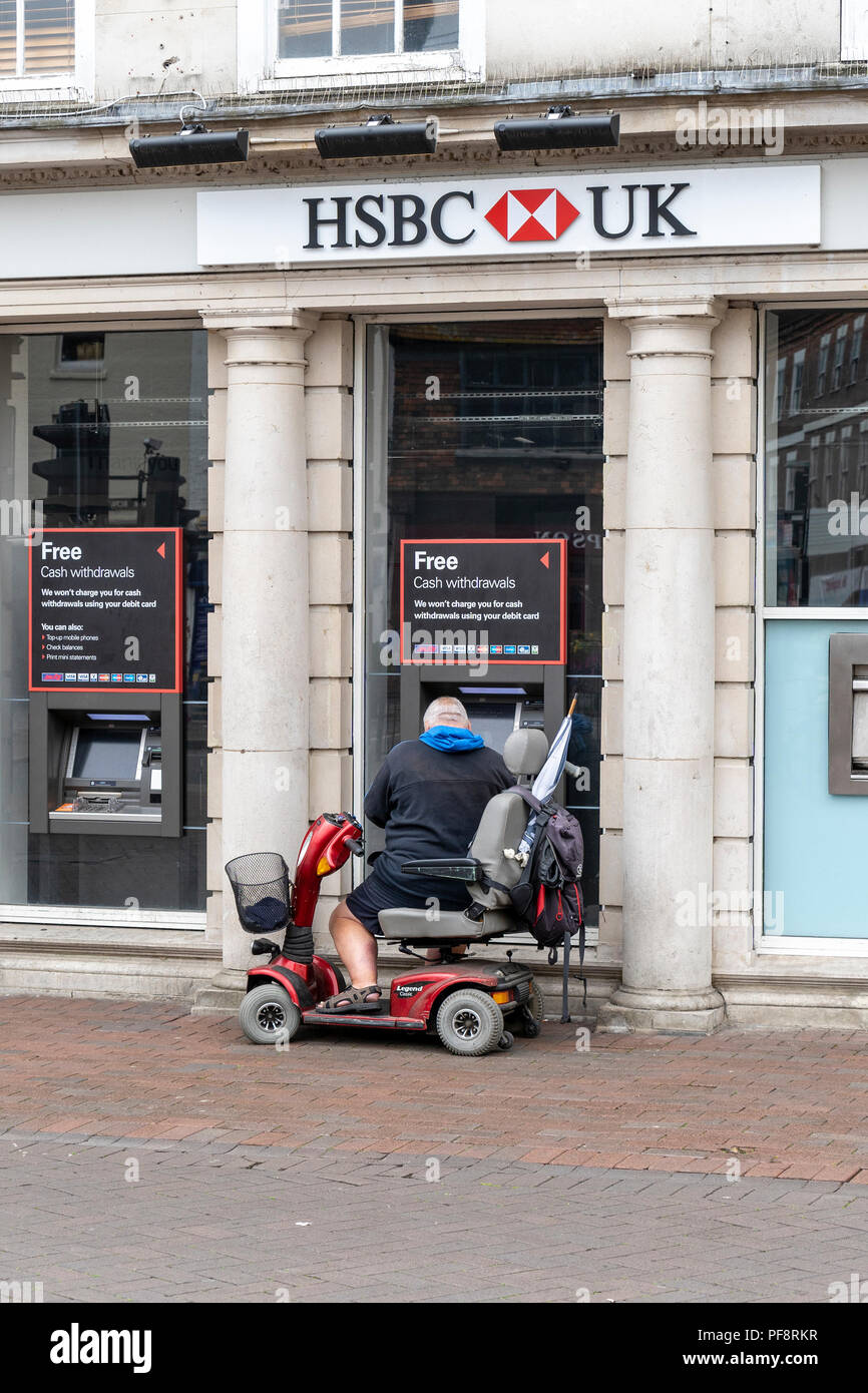 Man on mobility scooter using an ATM cash machine outside of a UK bank - Stock Image