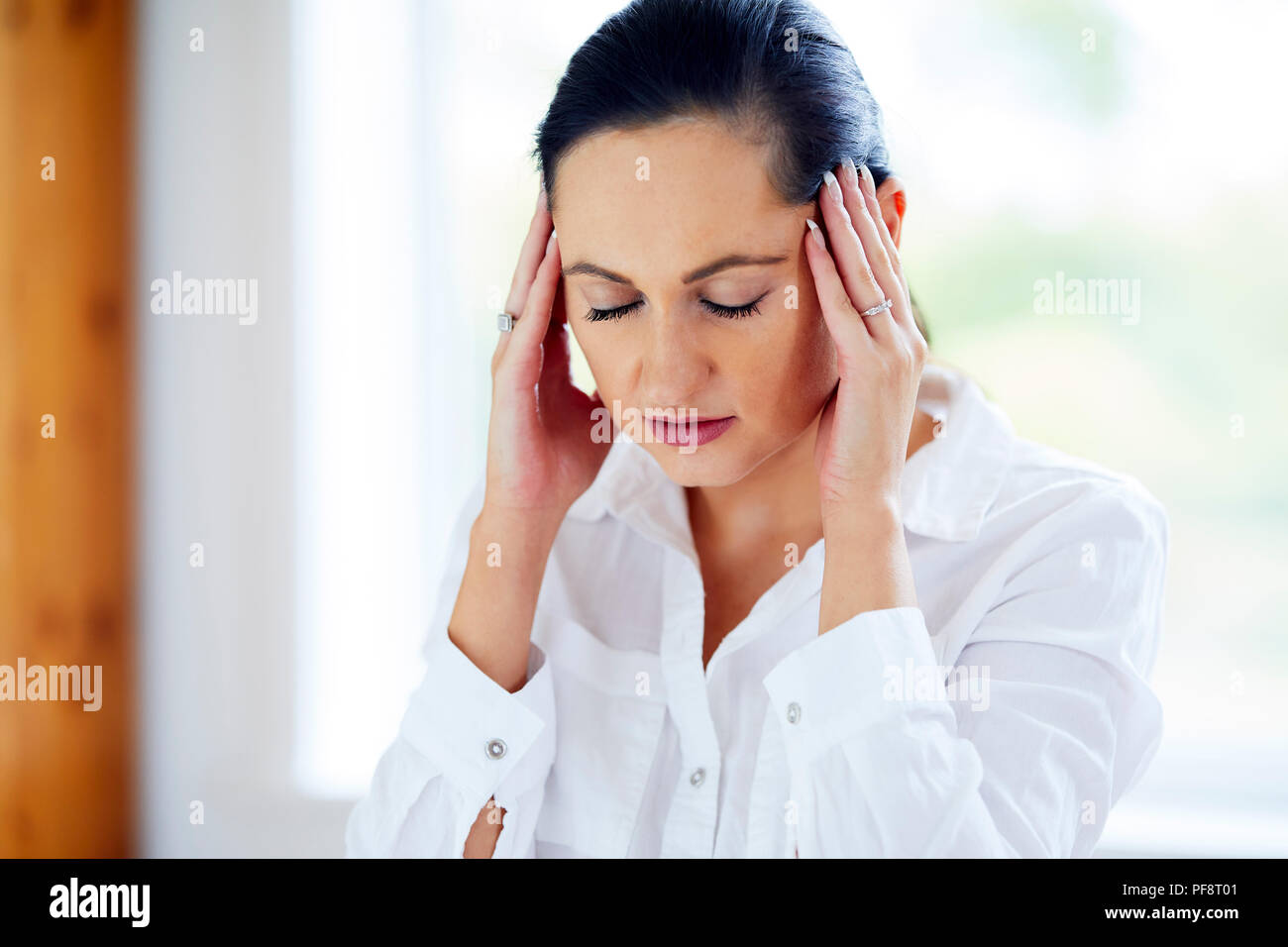 Woman rubbing her temples - Stock Image