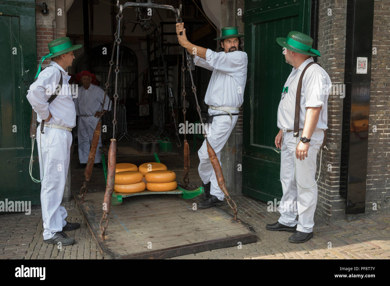 Alkmaar, Netherlands - July 20, 2018: Cheese carriers waiting for the cheeses to be weighted on the scale in the Waag building before being sold on th - Stock Image