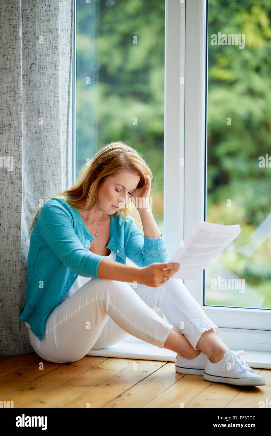 Woman looking worried holding a bank statement - Stock Image