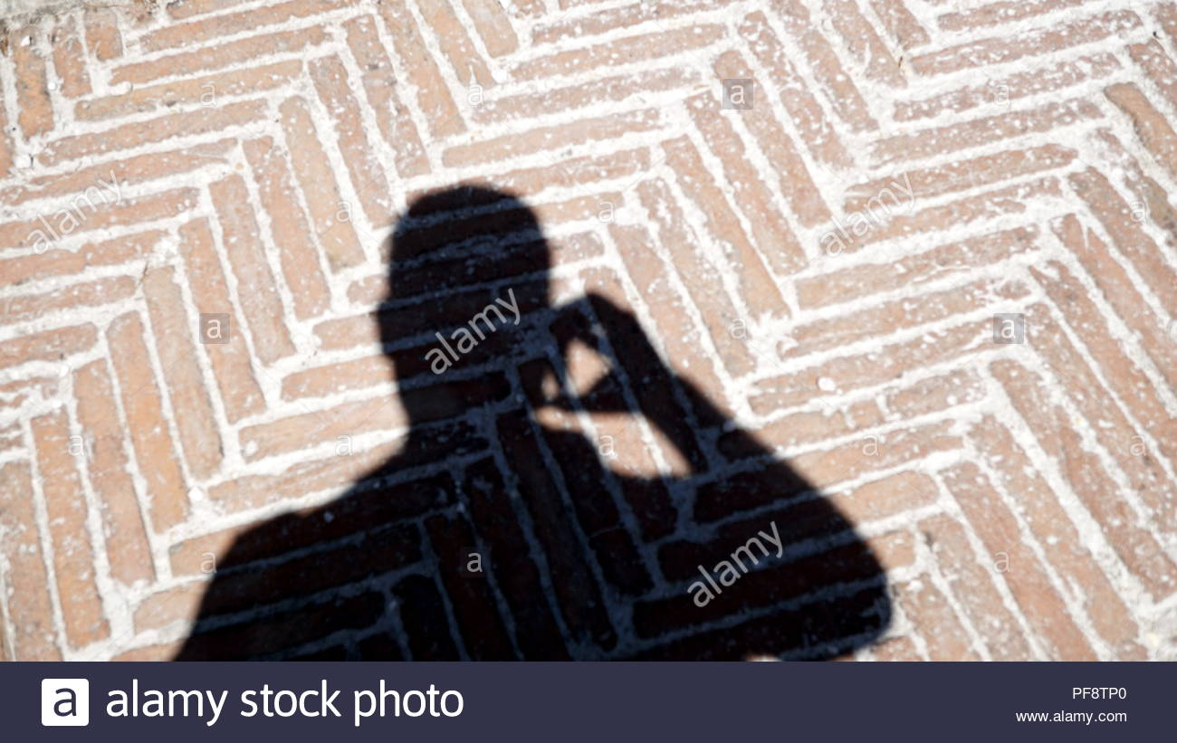 shadow of man talking on the phone projected on geometric flooring - Stock Image