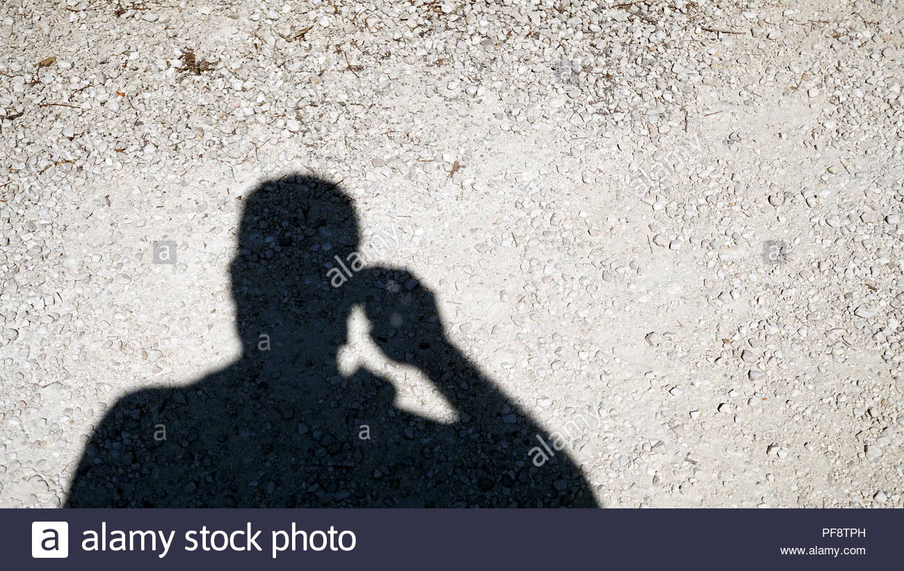shadow of man that take a picture,projected on floor with white pebbles in the sun - Stock Image