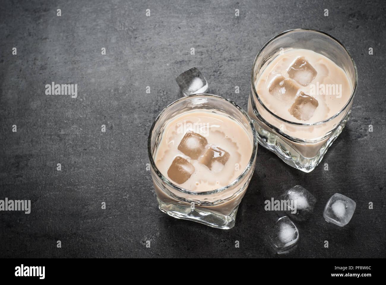 Irish cream liqueur in glasses with ice on black. Stock Photo