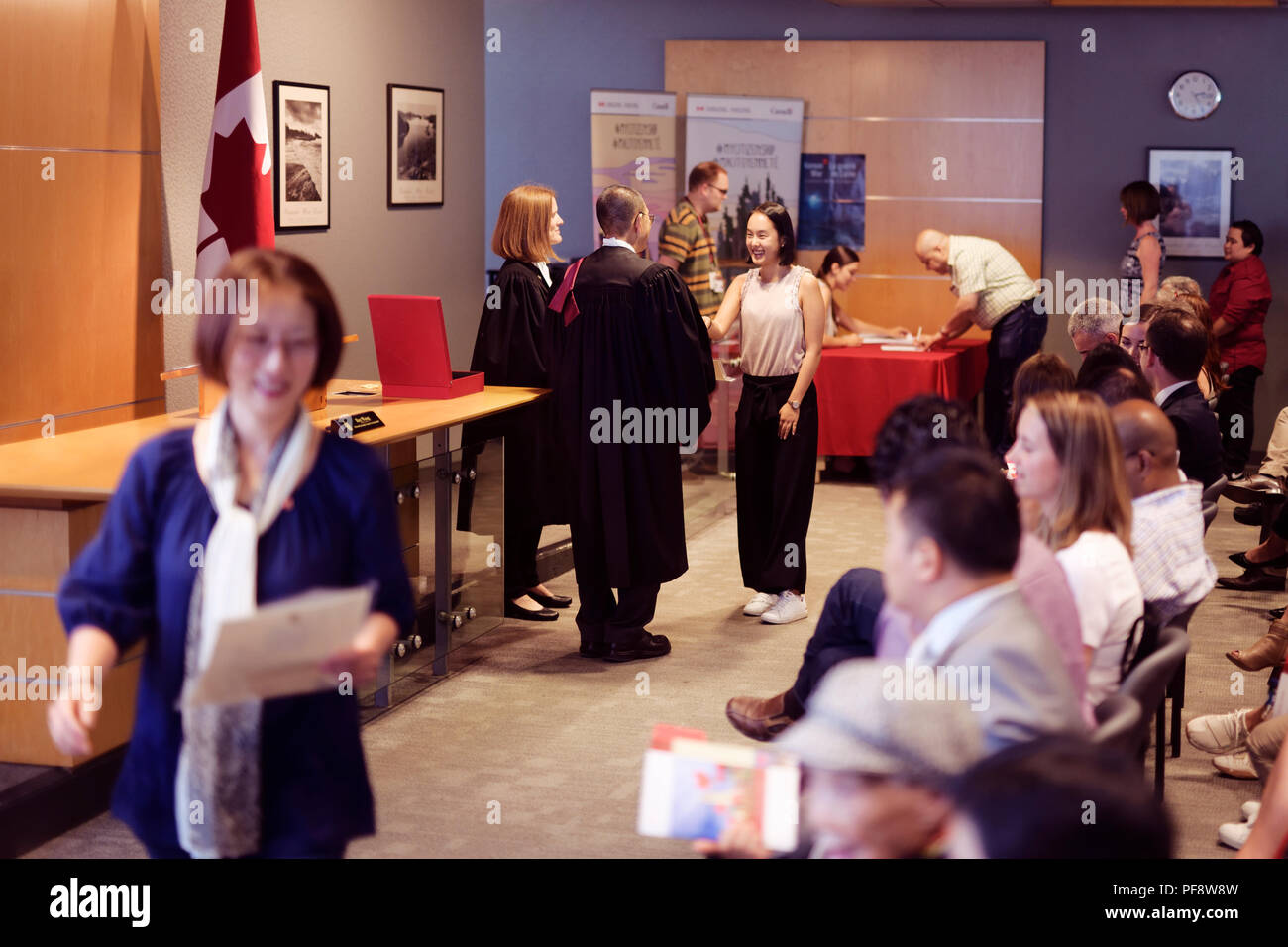New Canadian citizens receiving their Citizenship certificates at a Citizenship ceremony in Vancouver, British Columbia, Canada 2018 Stock Photo