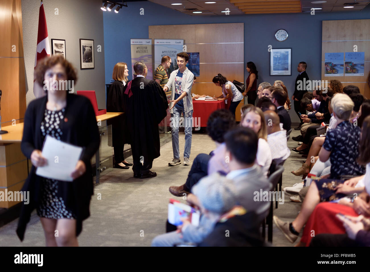New Canadian citizens receiving their Citizenship certificates from the judge in a Citizenship ceremony venue in Vancouver, British Columbia, Canada 2 - Stock Image