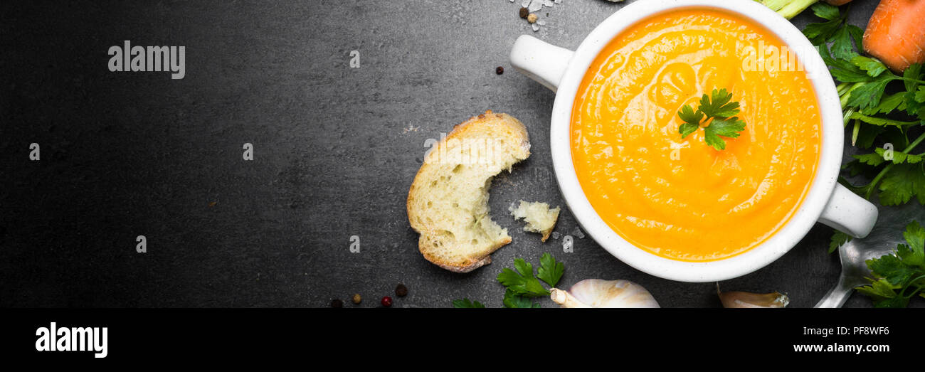 Carrot cream-soup on black table. Vegetarian vegetables soup. Top view. Long banner format. - Stock Image