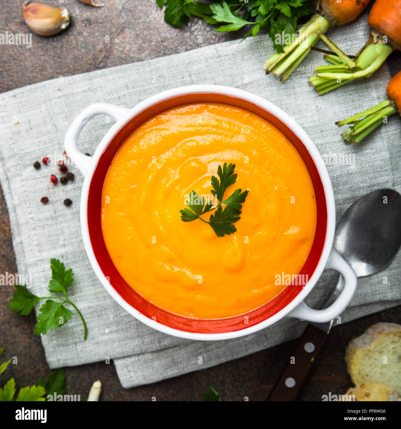 Carrot cream-soup on dark stone table. Vegetarian vegetables soup. Top view. Square. - Stock Image