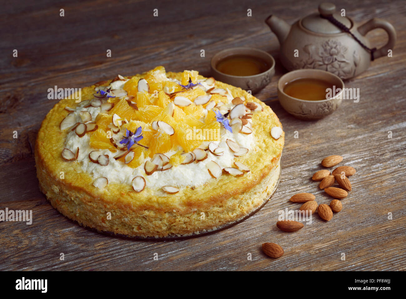 Healthy home-made flourless, sugar-free, dairy-free vegan cake made of almond flour, oranges and coconut, artistic food still life with a clay teapot  - Stock Image