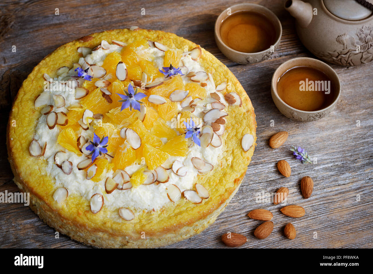 Healthy home-made flourless, sugar-free vegan fruit cake made of almond flour, oranges and coconut oil, artistic food still life on rustic wooden tabl - Stock Image