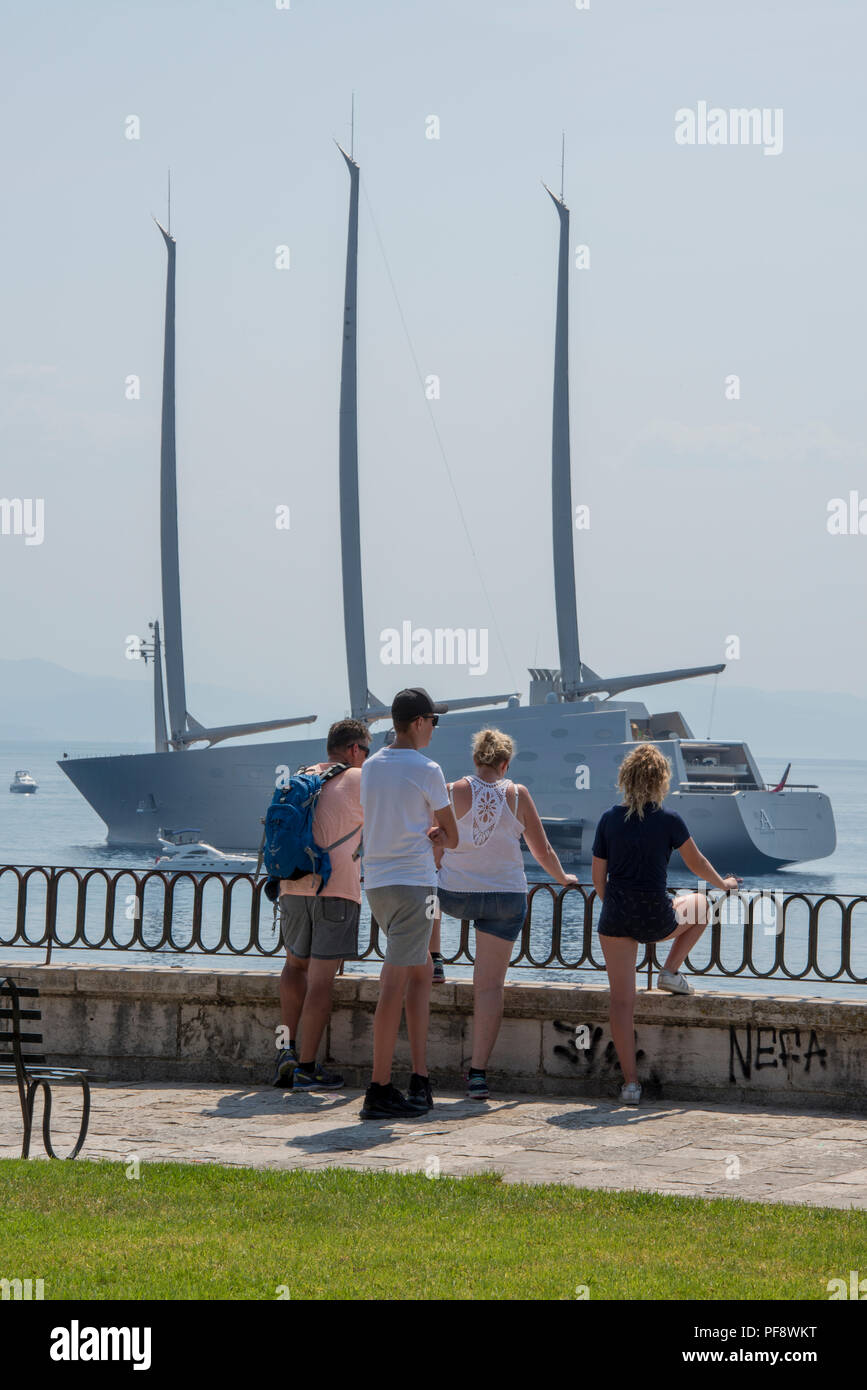 Family looking at sailing yacht A owned by russian billionaire Andrey Melnichenko at anchor in the bay off of the greek island of corfu in greece. Stock Photo