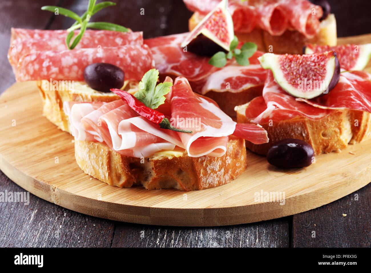 Sandwich with prosciutto or salami or crudo. Antipasti gourmet bruschetta snack - Stock Image