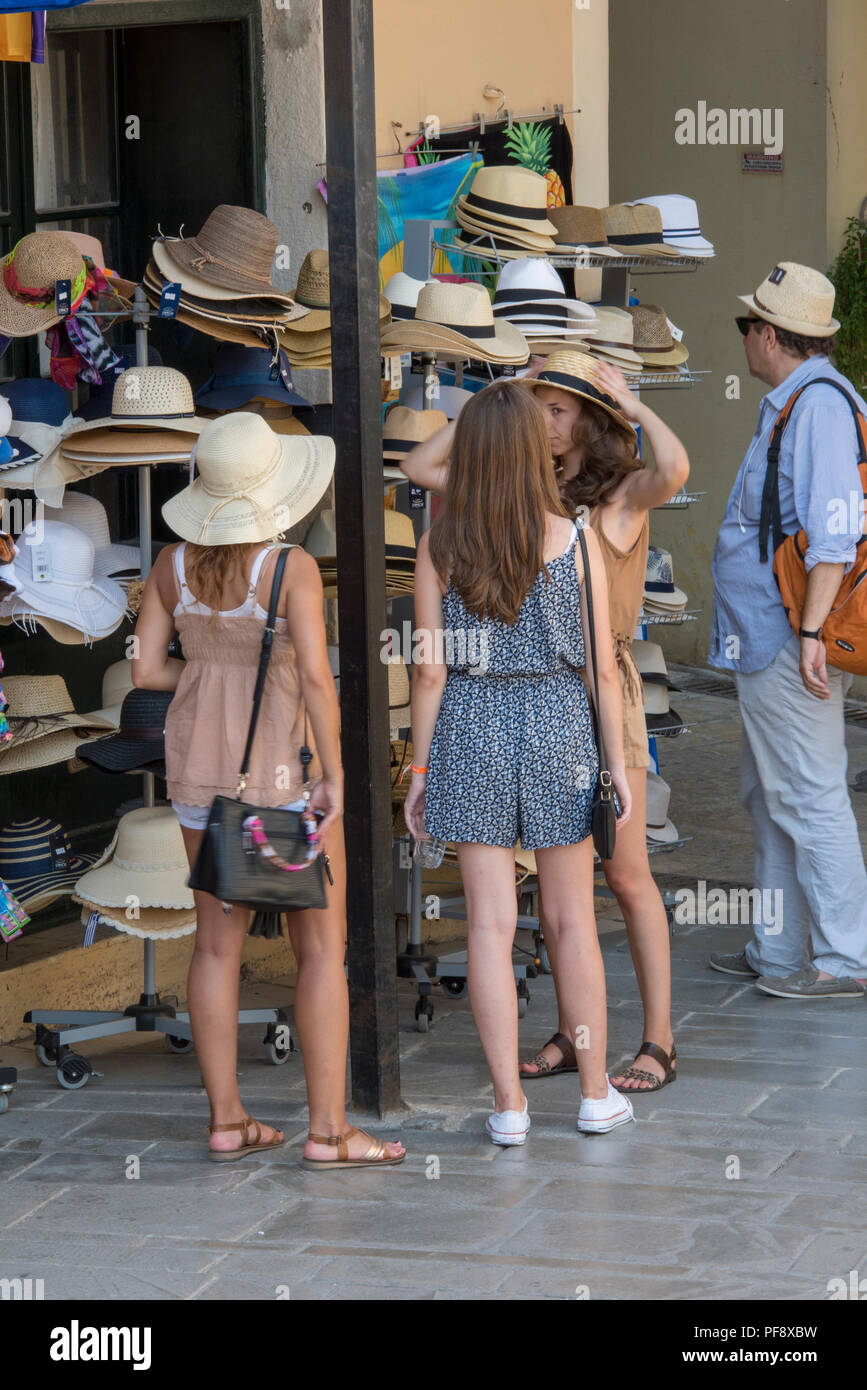 three attractive young women on holiday trying on hats at a souvenir shop in kerkyra, corfu, Greece. - Stock Image