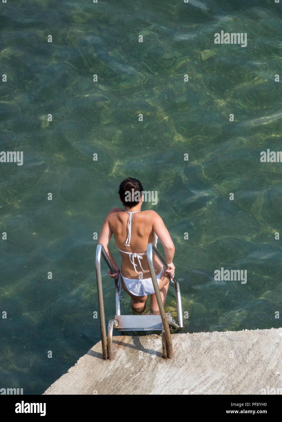 an attractive young woman wearing a bikini or swimming costume entering the sea or water using a ladder. - Stock Image