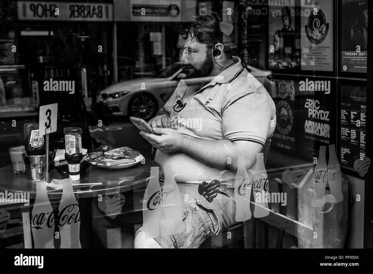 Man Eats Breakfast Whilst Using Phone In Manchester City Centre, England, UK - Stock Image