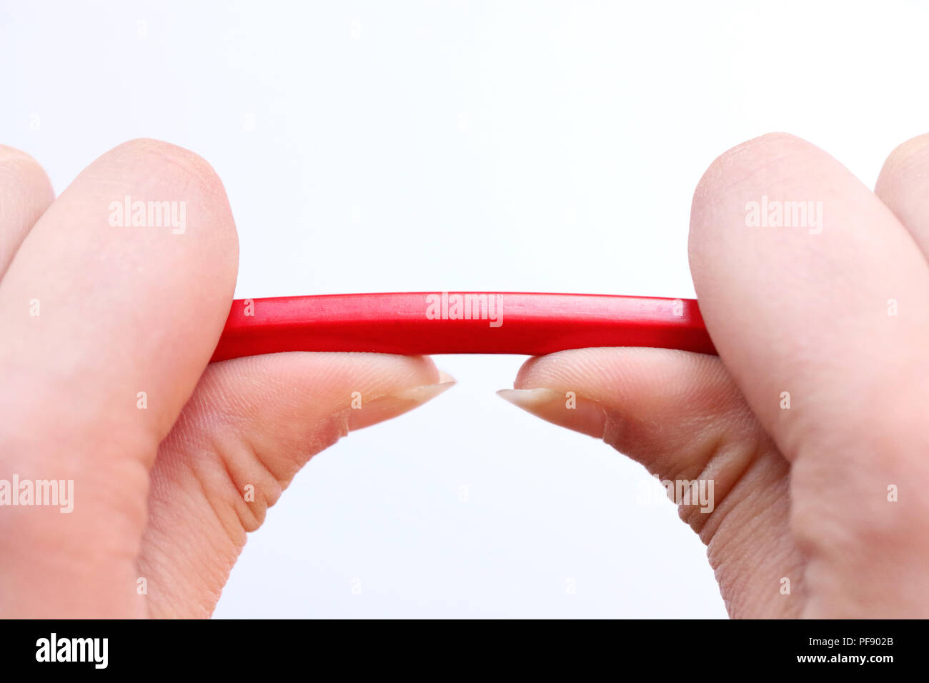two hands holding a red pencil about to snap under the pressure. Concept of stress, anger management, pressure in the work place, parenting and breakd - Stock Image