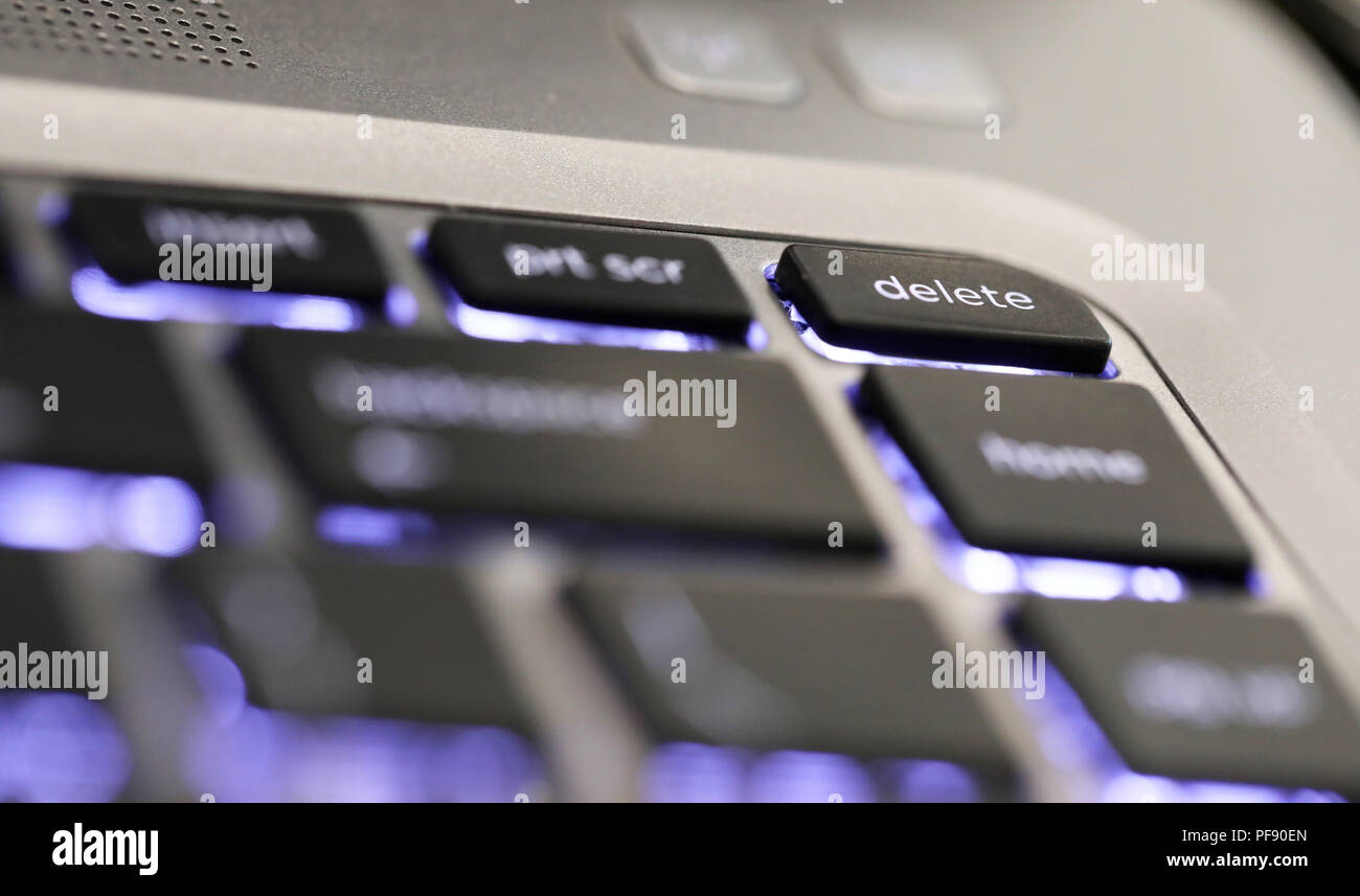 close up of  the delete symbol button tab on an illuminated laptop computer key board. The delete key - Stock Image