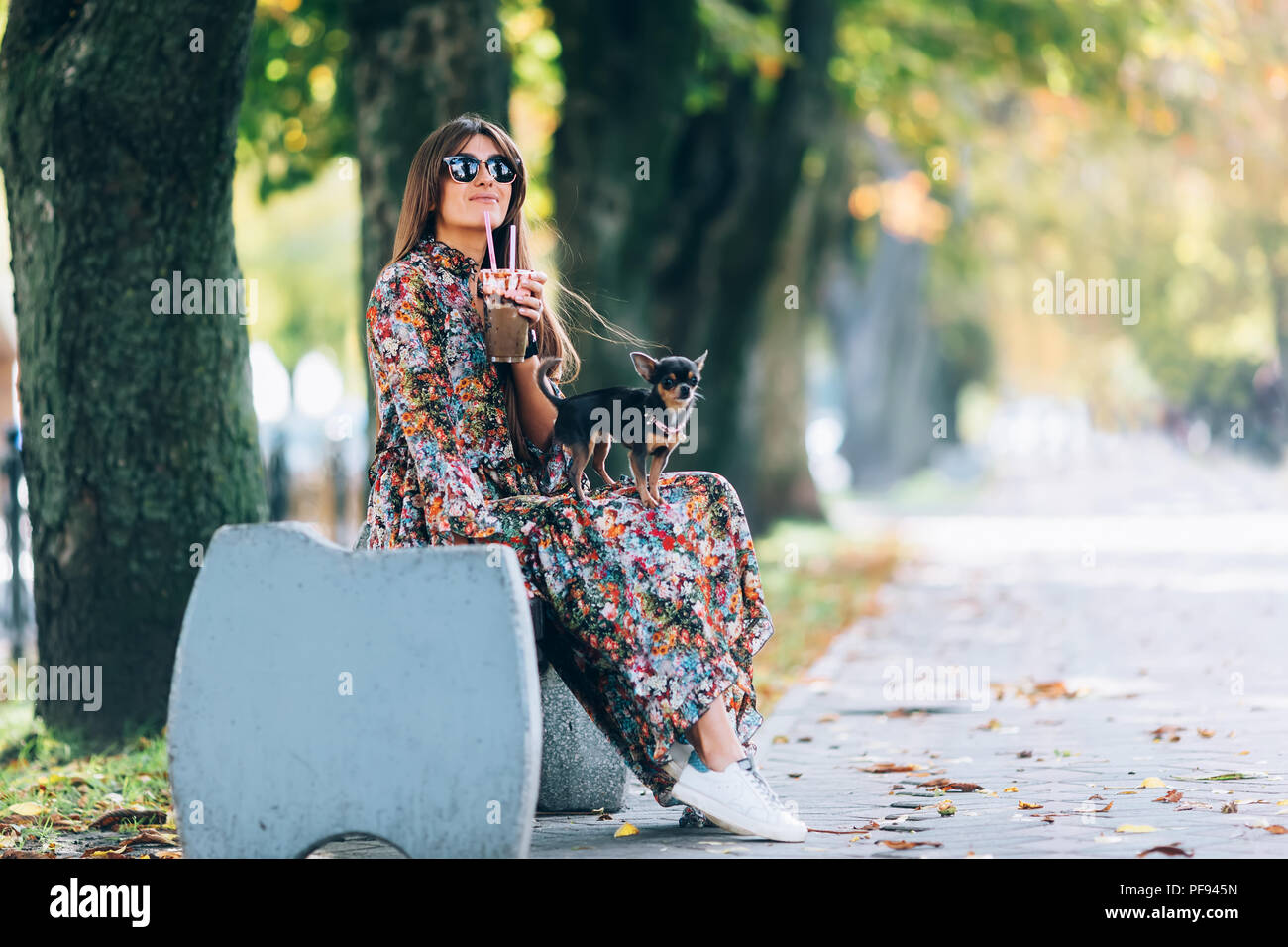 Young woman in sunglasses with milkshake. Outdoor lifestyle portrait of pretty smiling female with little puppy in autumn park Stock Photo