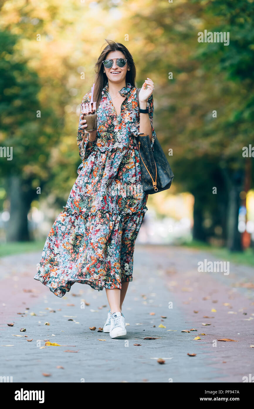 Young woman in sunglasses with milkshake. Outdoor lifestyle portrait of pretty smiling female walking in autumn park - Stock Image