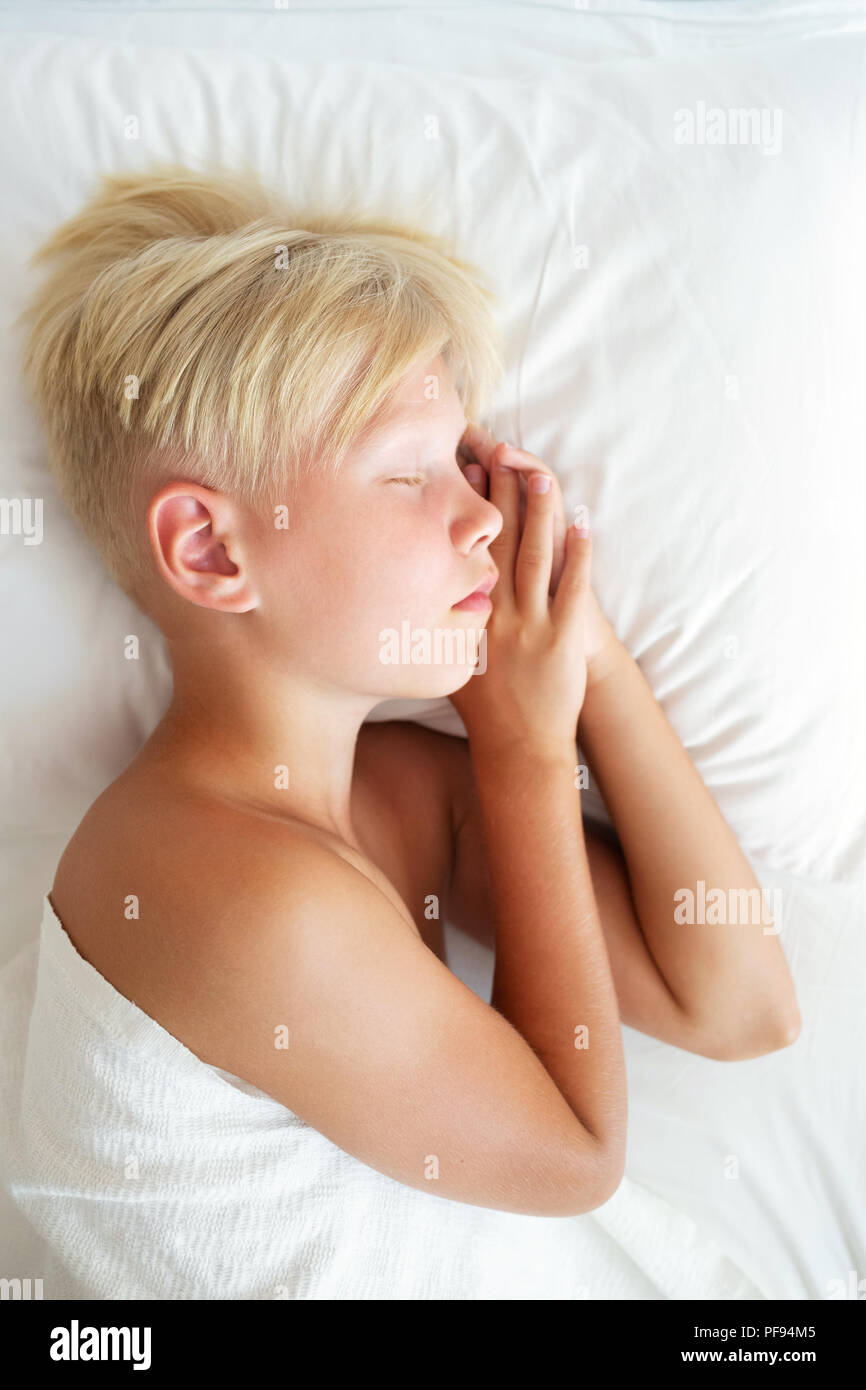 Blondy boy sleeping in bed. Sweet dream concept. Top view. - Stock Image