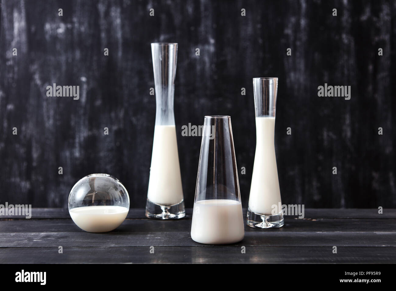 Glass containers of different shapes with white liquid or milk on a black background with place under text. Concept of jewish holiday Shavuot. - Stock Image