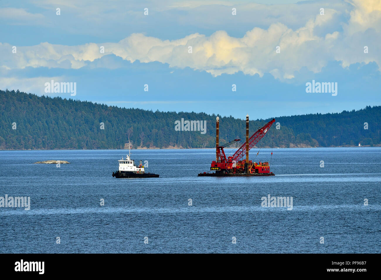 A tug boat hauling a barge with a crane onboard traveling through the Strait of Georgia near Vancouver Island on British Columbia's Pacific coast. - Stock Image