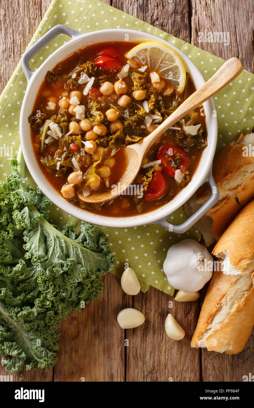 Stewed kale cabbage with chickpeas and vegetables close-up on the table. Vertical top view from above Stock Photo