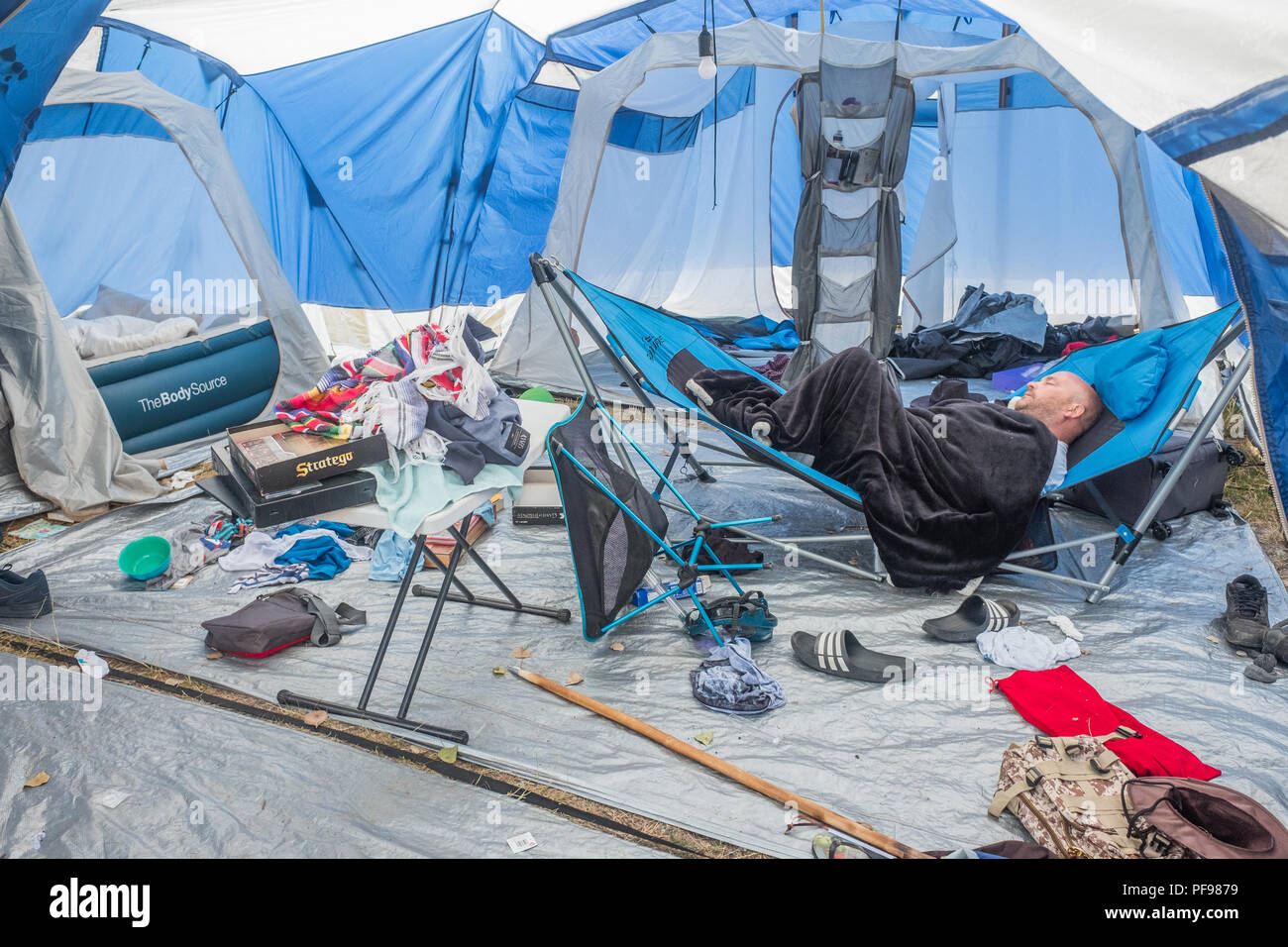 Man sleeps on a camp bed in an untidy interior of a large tent, with clothes, chairs, and equipment strewn all over the place. - Stock Image