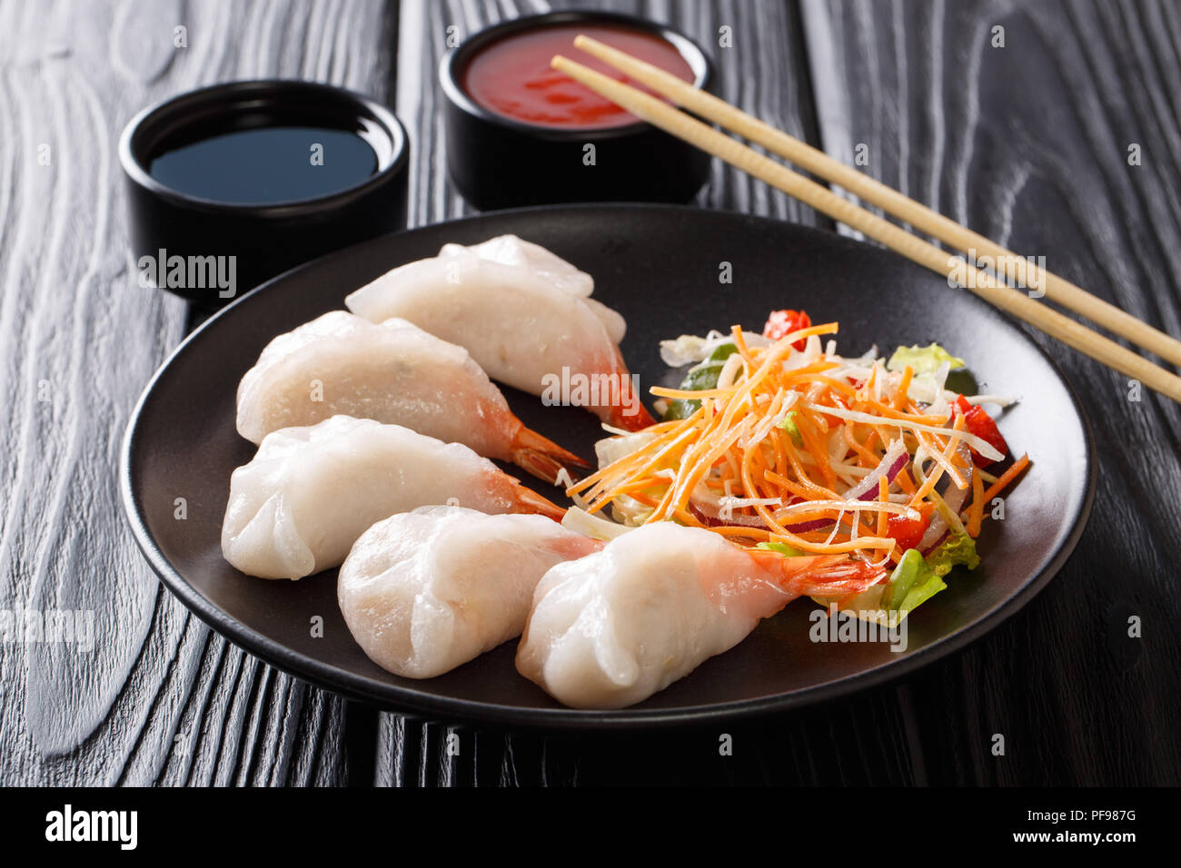 jiaozi, gyoza dumplings with prawns close-up served with vegetable and soy and tomato sauces on the table. horizontal - Stock Image