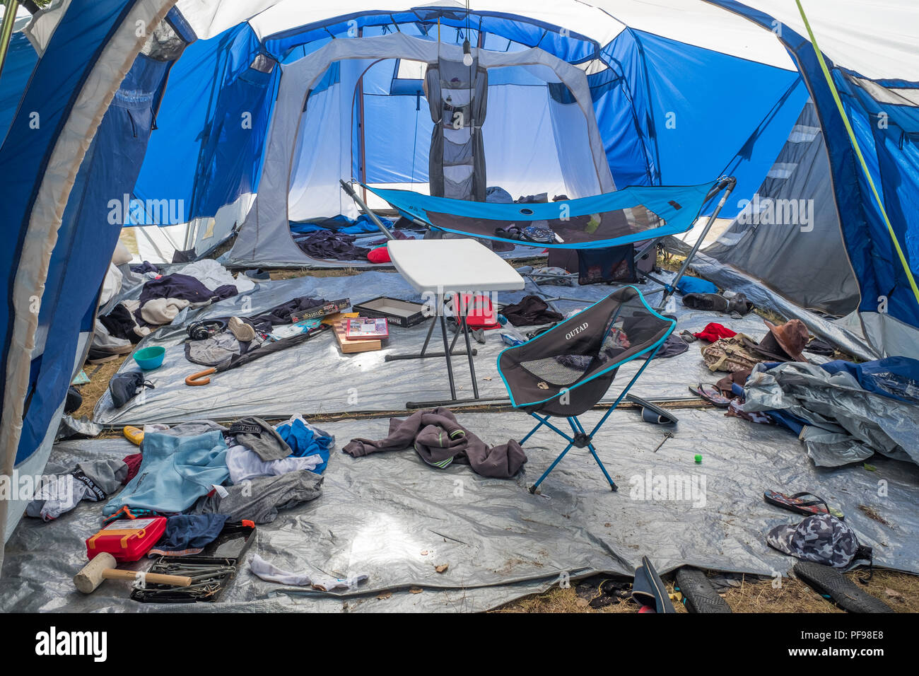 Untidy interior of a large tent, with clothes, chairs, and equipment strewn all over the place. - Stock Image