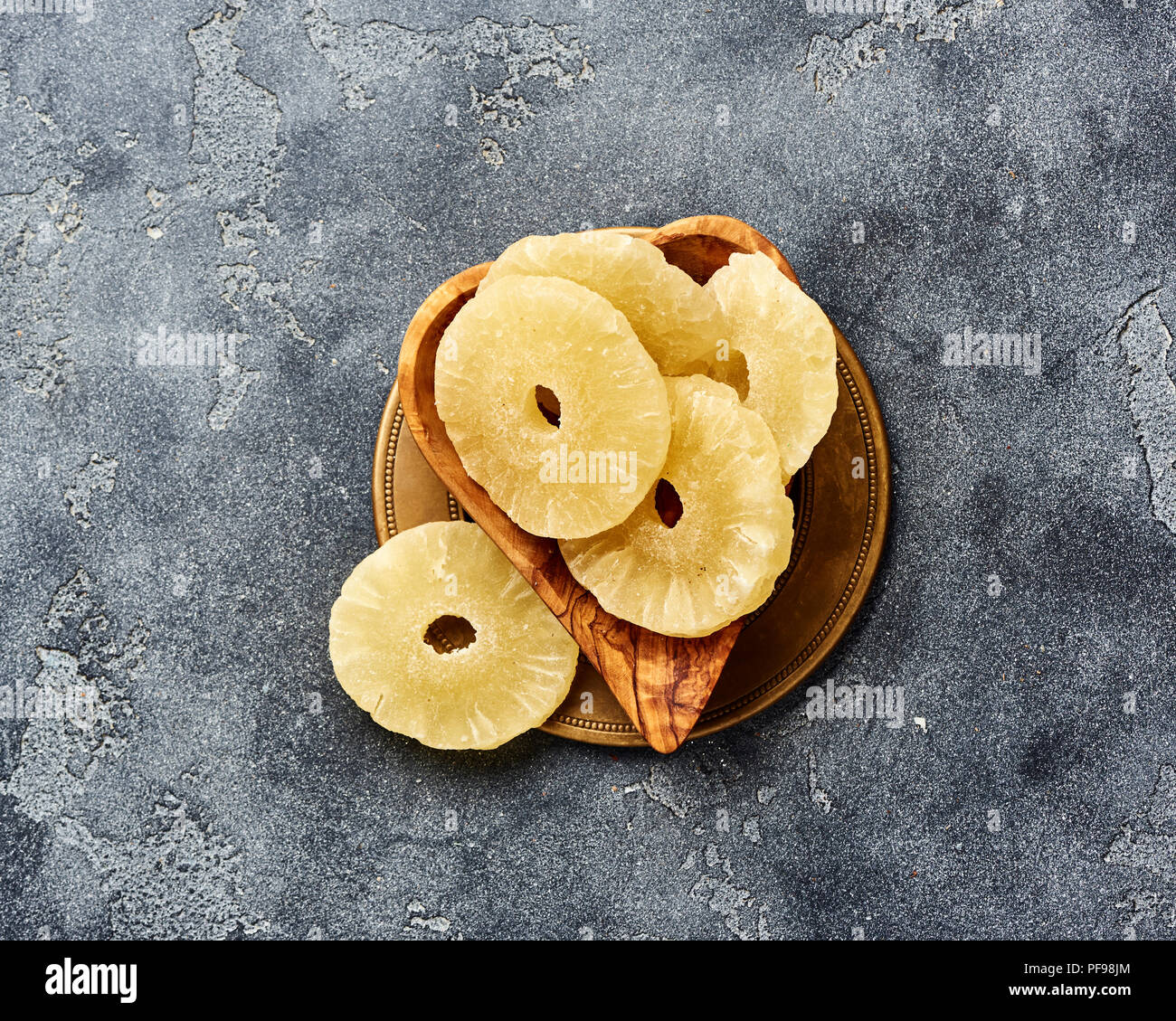 Dried pineapple rings on a gray table. Top viw of sweet paneapple slices. - Stock Image