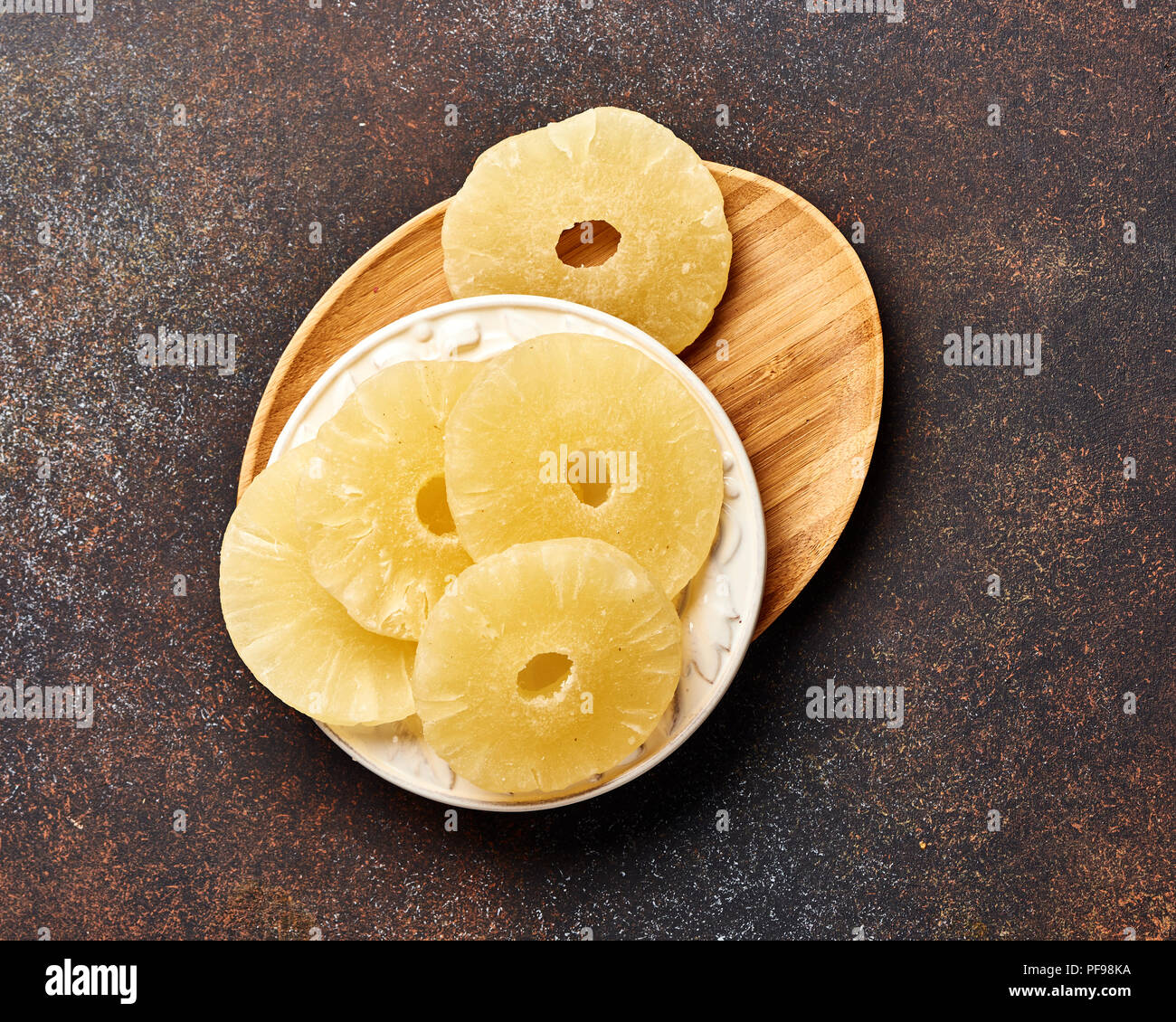 Dried pineapple rings on a brown table. Top viw of sweet paneapple slices. - Stock Image