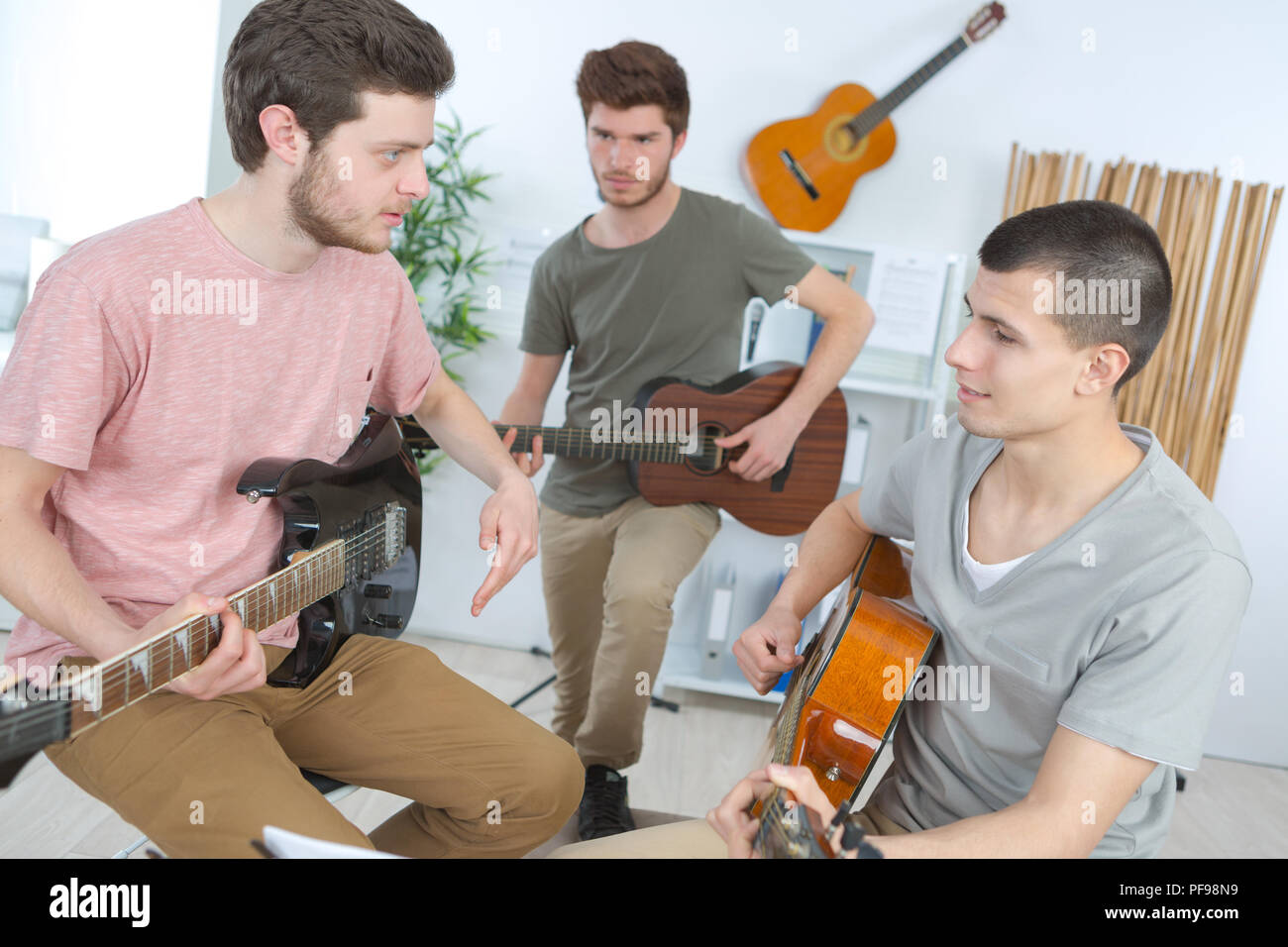 friends playing guitars together - Stock Image