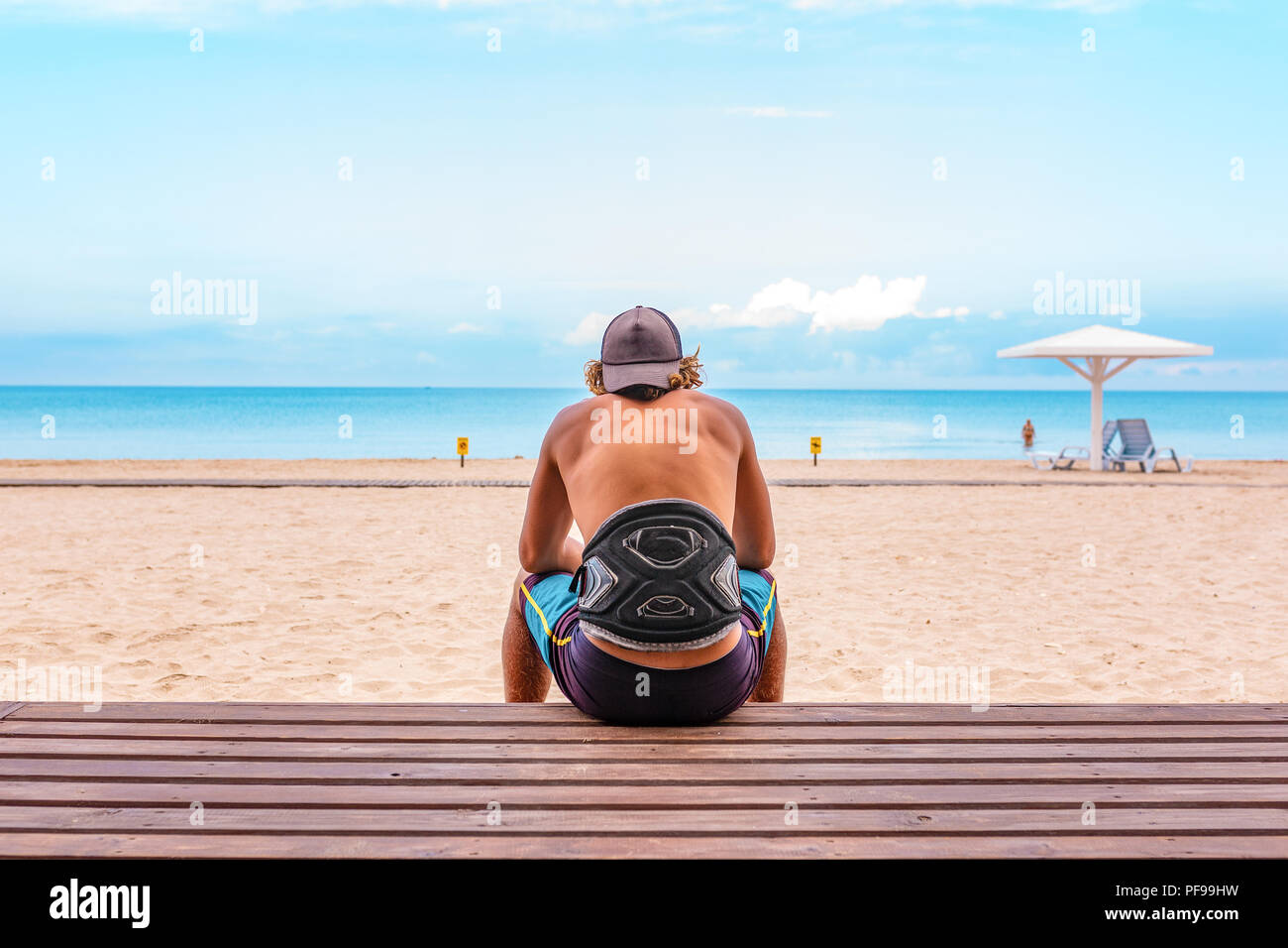 The surfer sits with his back to the camera on the terrace on the beach looking out into the distance, - Stock Image