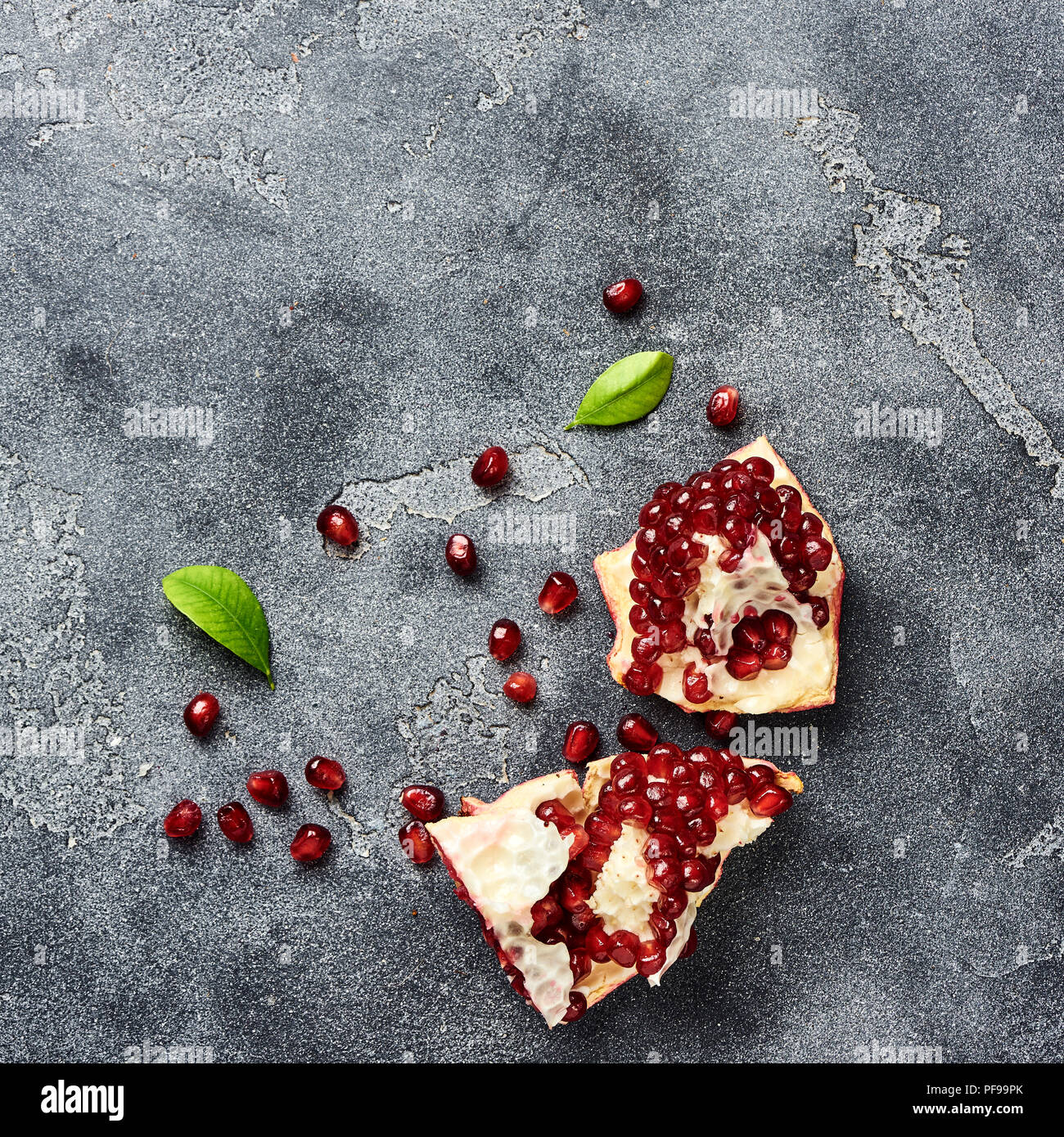 Pomegranate fruit with seeds on gray background with copy space. Top view. - Stock Image