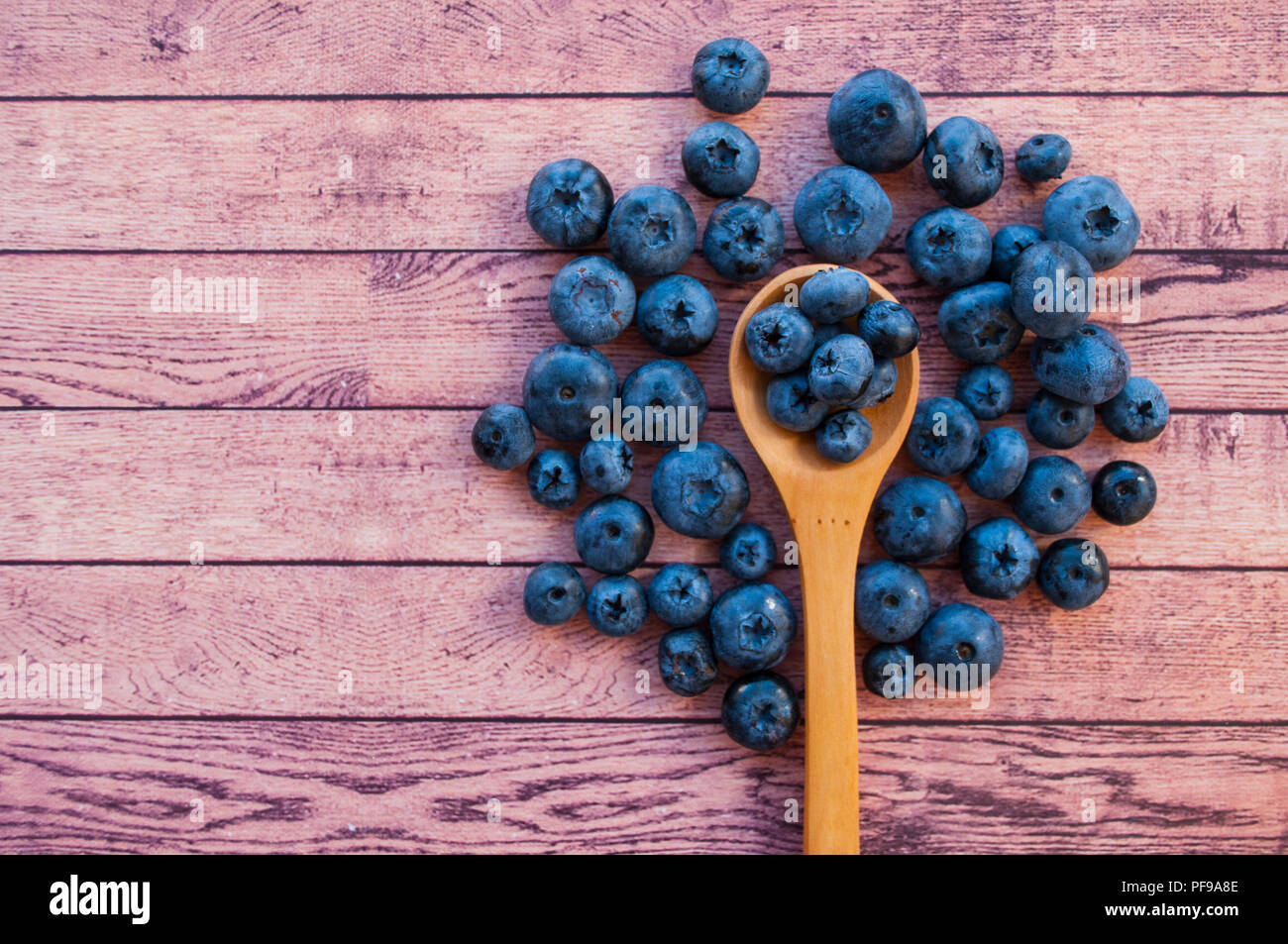 Fresh and juicy blueberries in a wooden spoon on wooden table with copyspace. Healthy food concept. - Stock Image