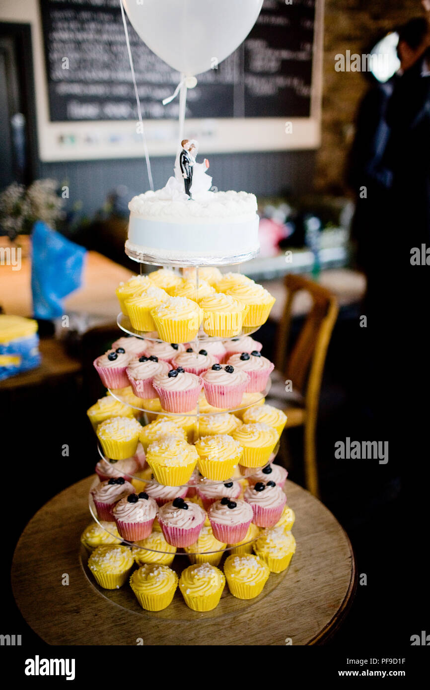 Modern wedding cake featuring tiers of a cake with cupcakes and ...