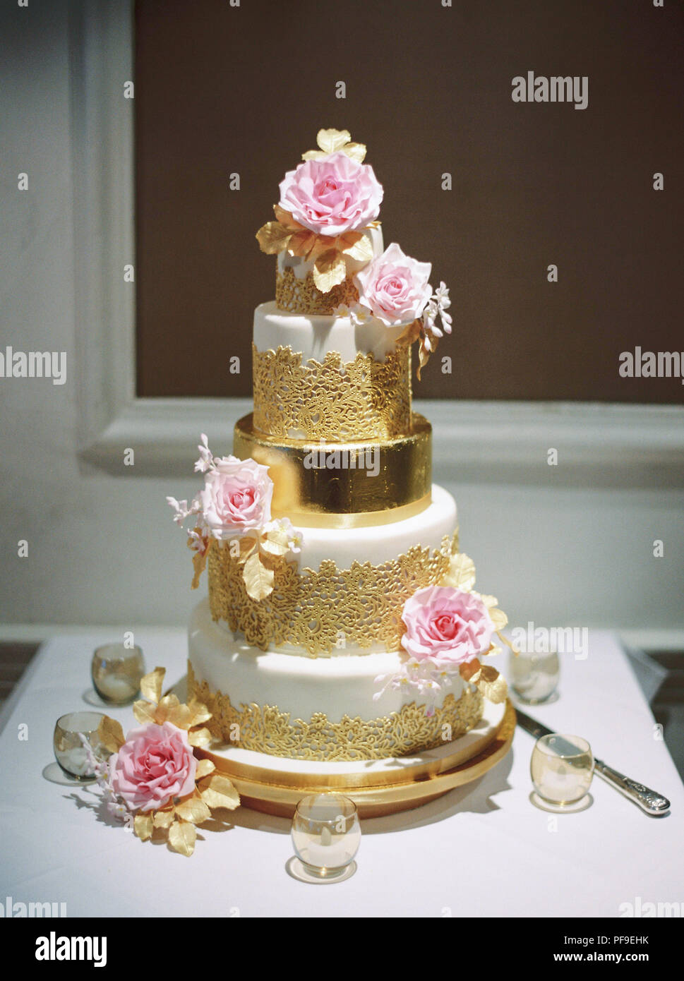 gold white pink tiered wedding cake with roses - Stock Image