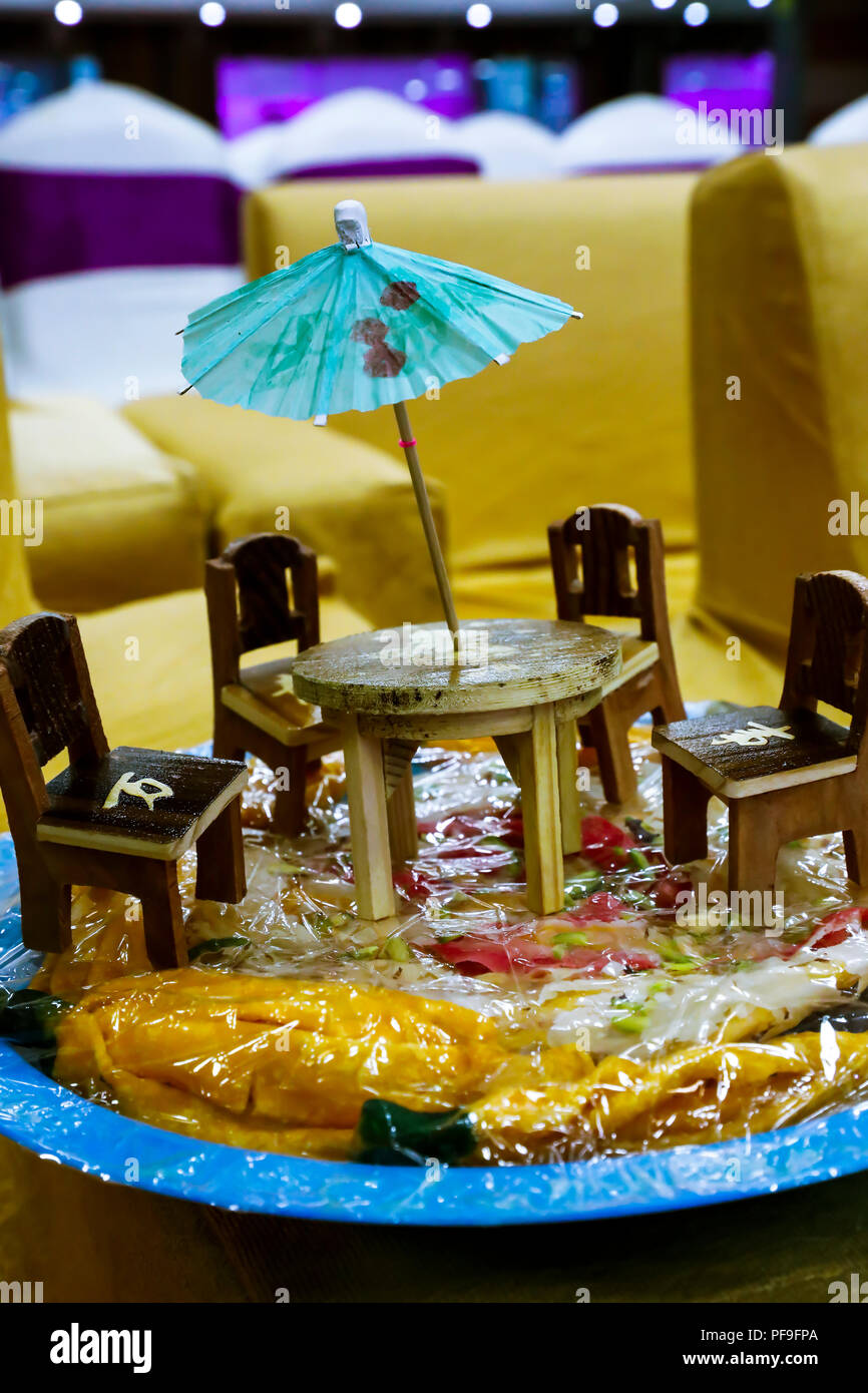 miniature of home furniture displayed on a traditional sweet delicacy base to gift bride and groom in wedding - Stock Image