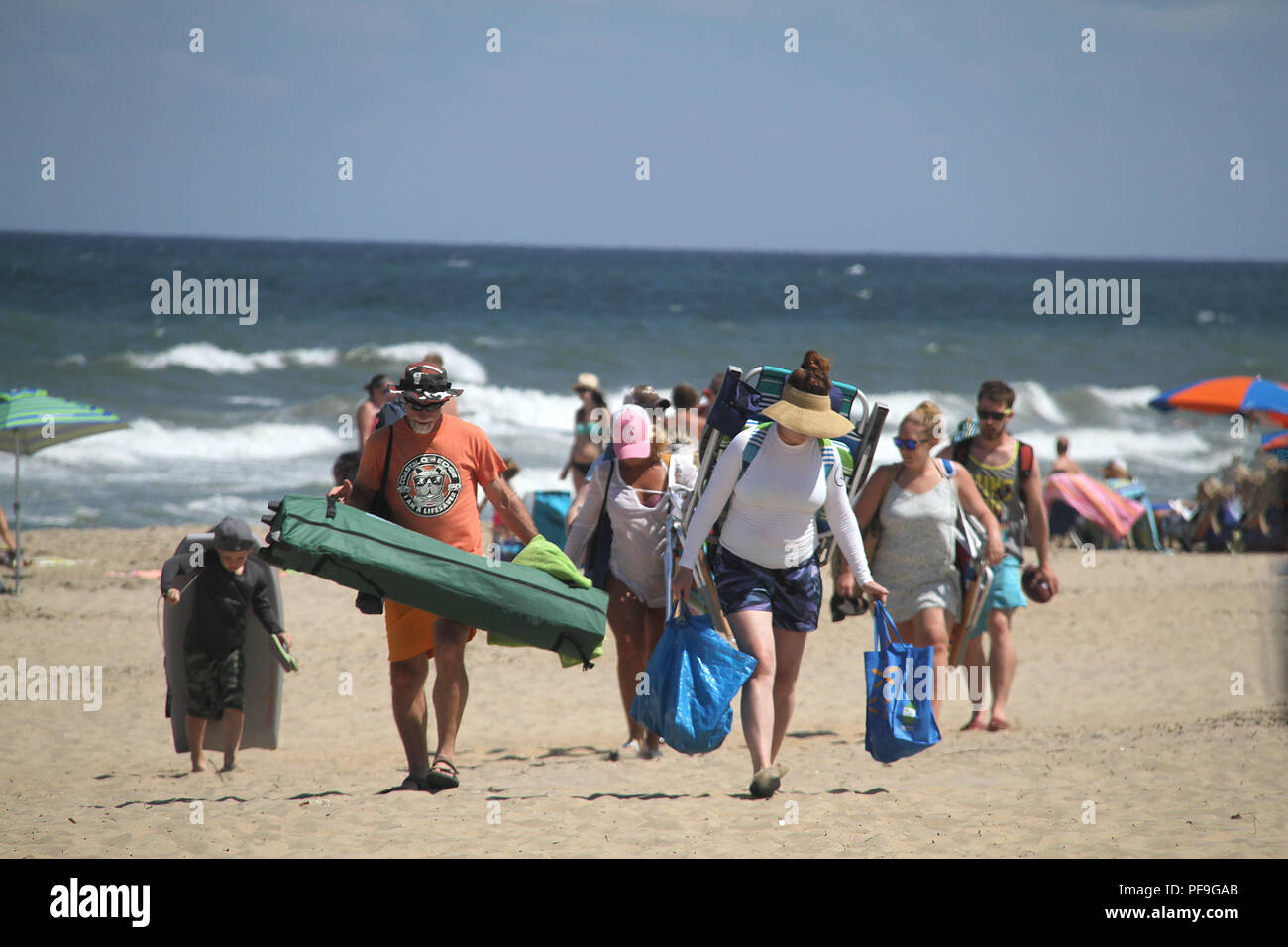 People leaving the beach carrying their items, bags, seats, and floaties - Stock Image