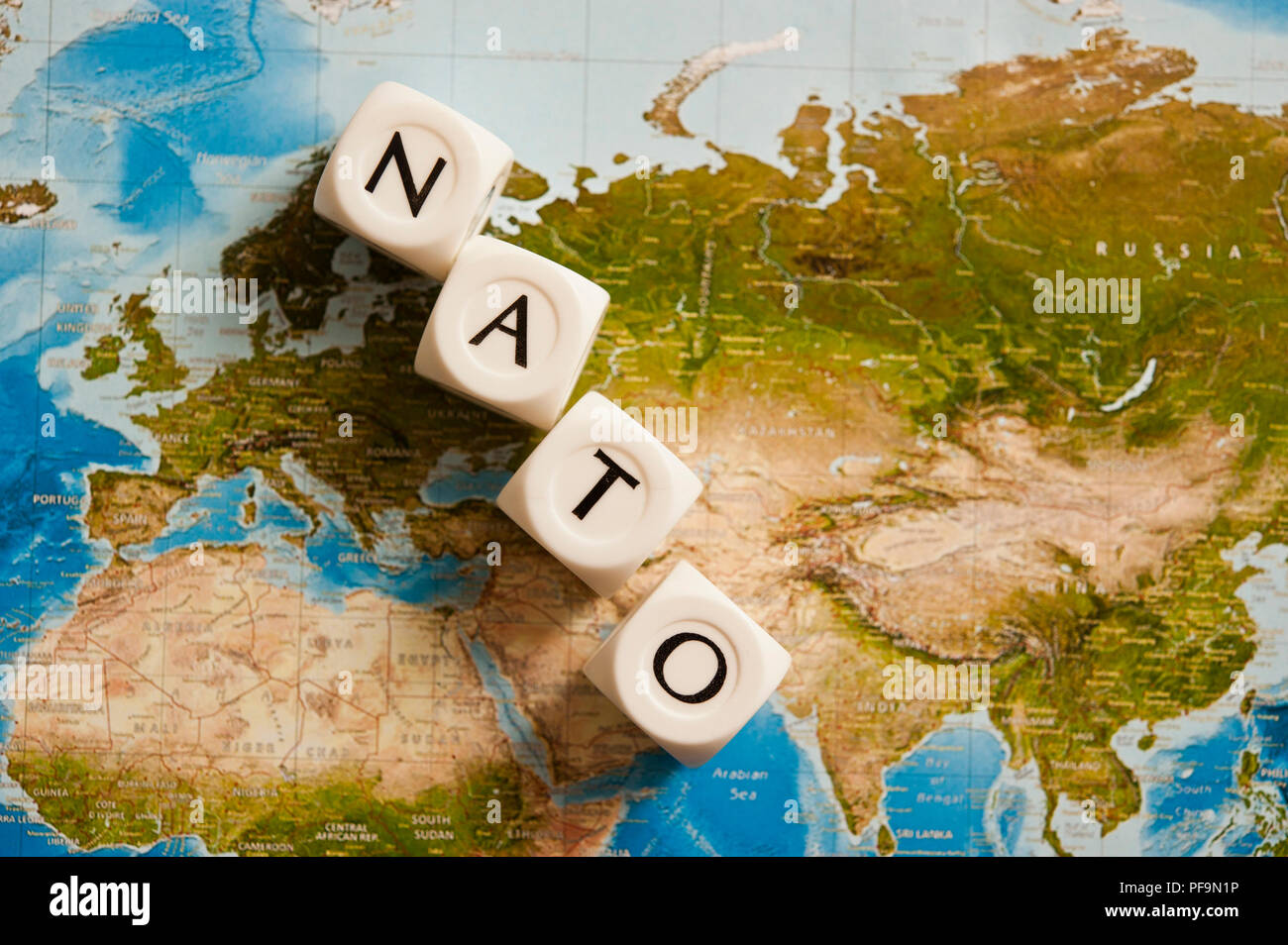 NATO spelled with dice on a world map, concept for the North Atlantic Treaty Organization expanding its members - Stock Image