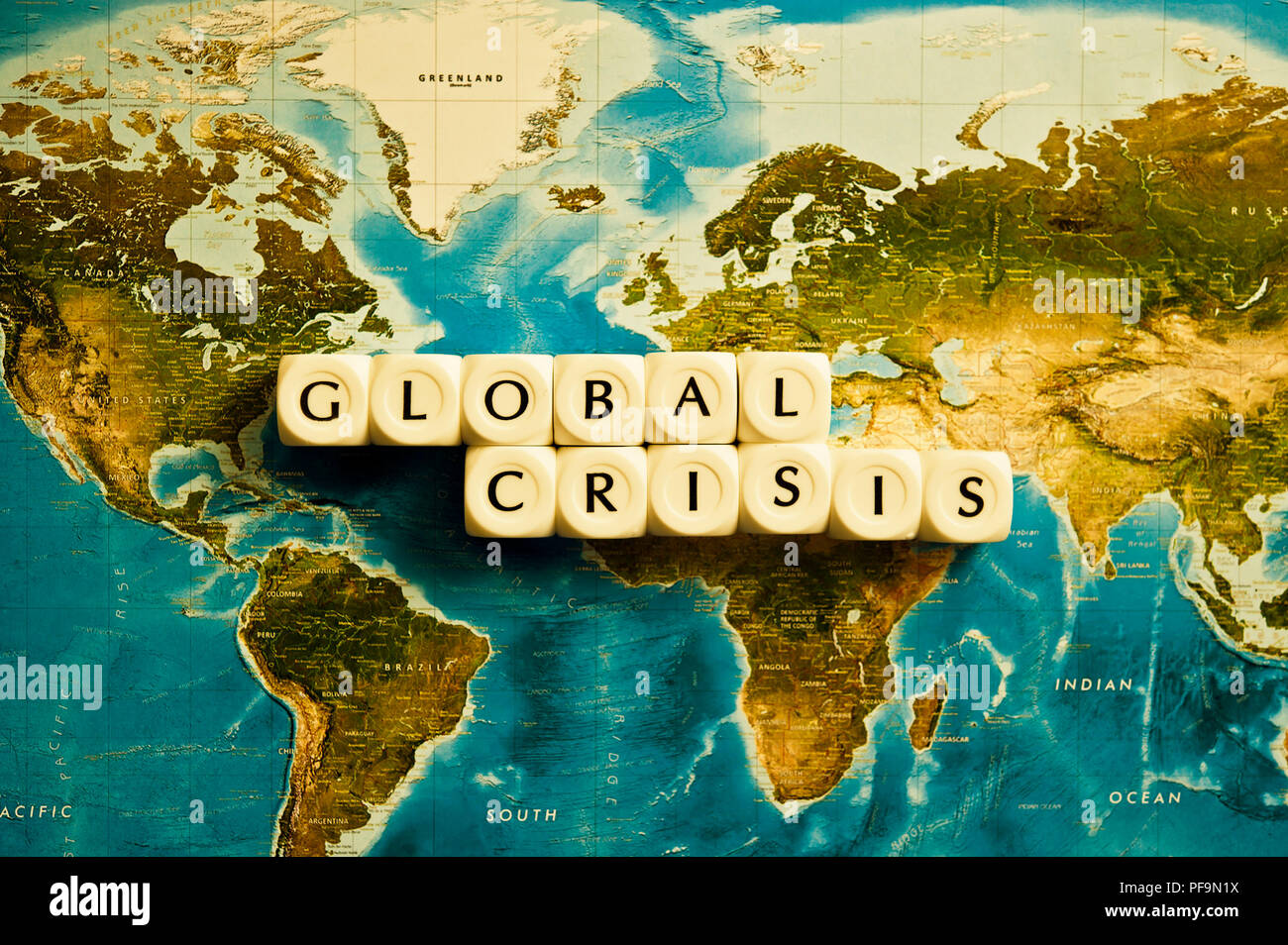 map of world and Global Crisis words spelled with dice - Stock Image