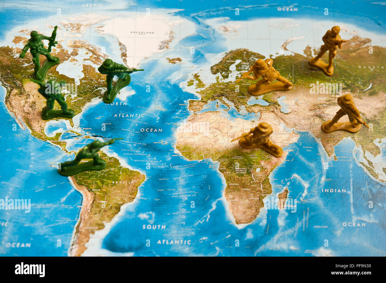toy plastic soldiers armies facing each other on a world map - Stock Image